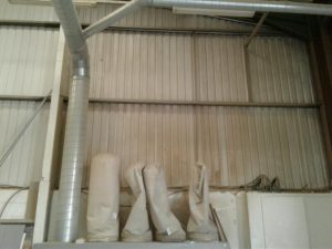 Photos showing before and after cleaning of warehouse walls and ceiling
